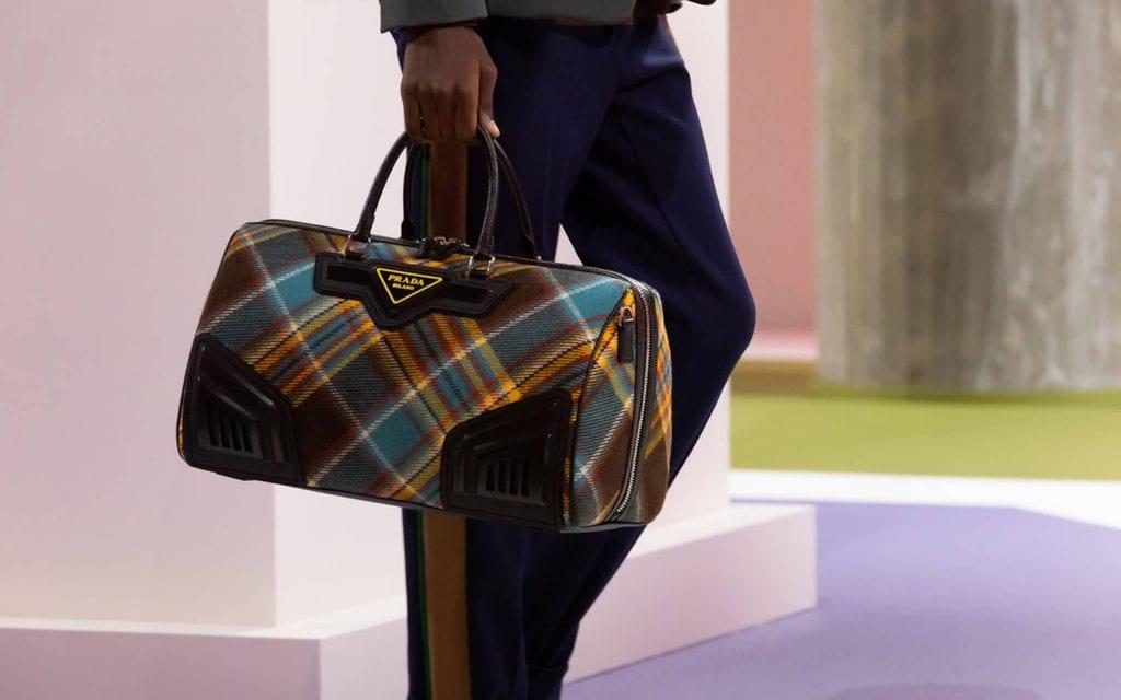 Man holding a Prada bag