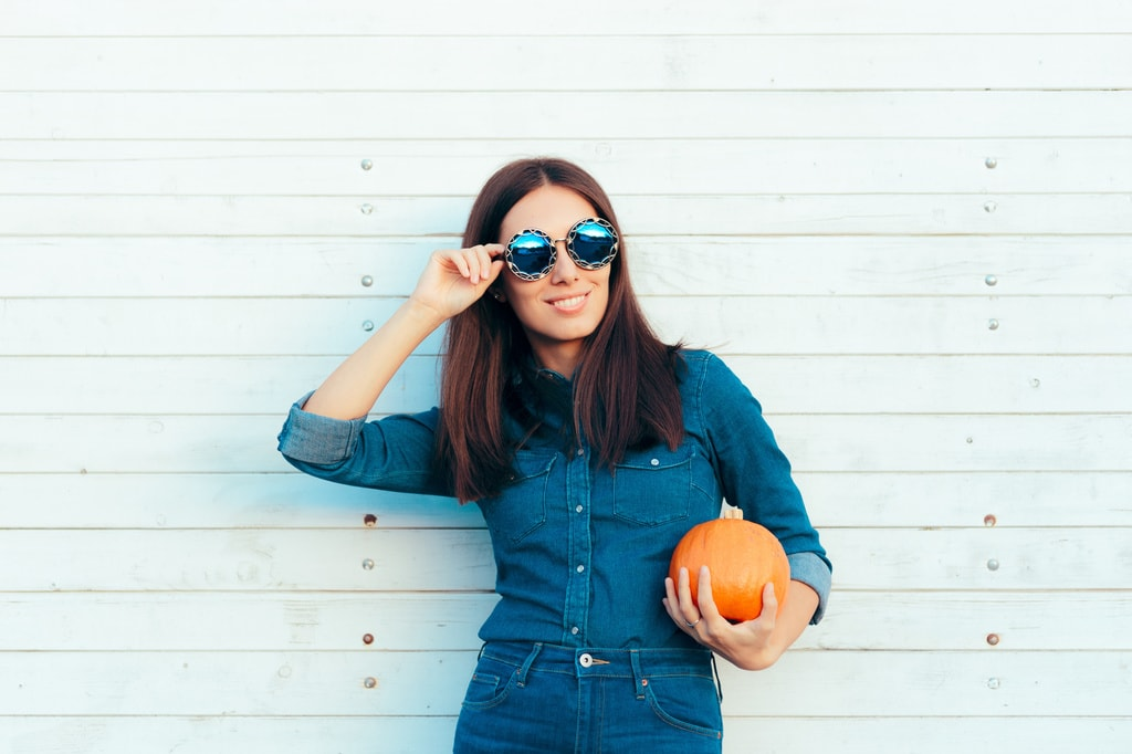 Cool Autumn Girl in Denim Outfit and Sunglasses Holding Pumpkin