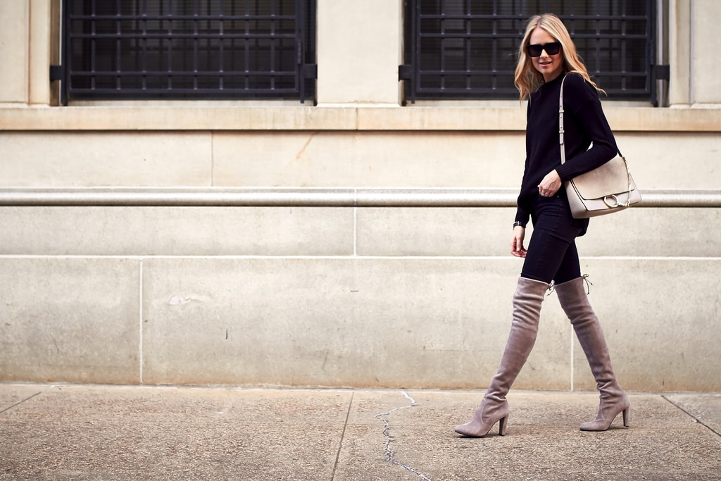 Woman wearing pants tucked into beige knee-high boots