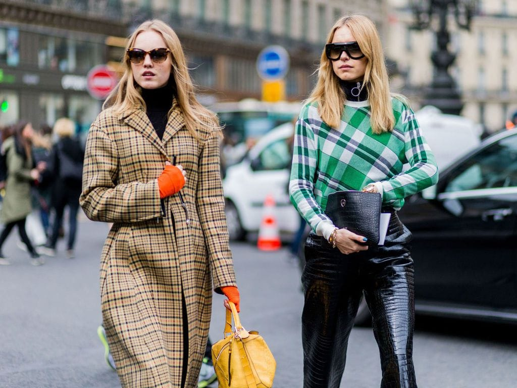 Two women wearing black turtle neck blouses