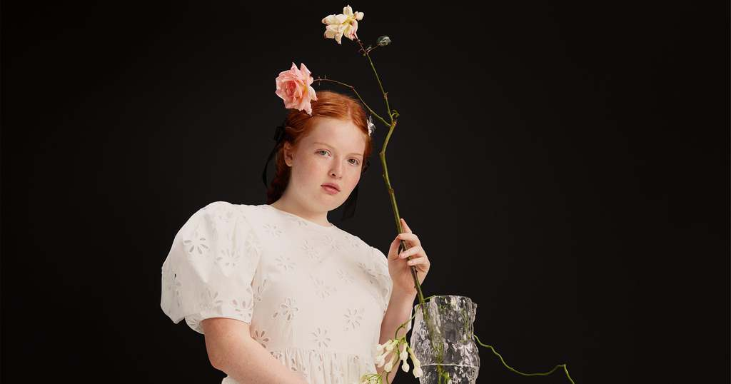 A model posing in a floral dress from the H&M x Simone Rocha collection