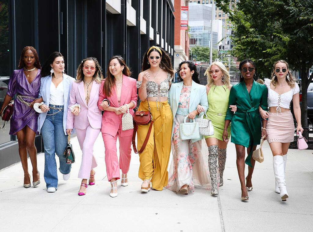 Young women walking on the pavement wearing different spring outfits