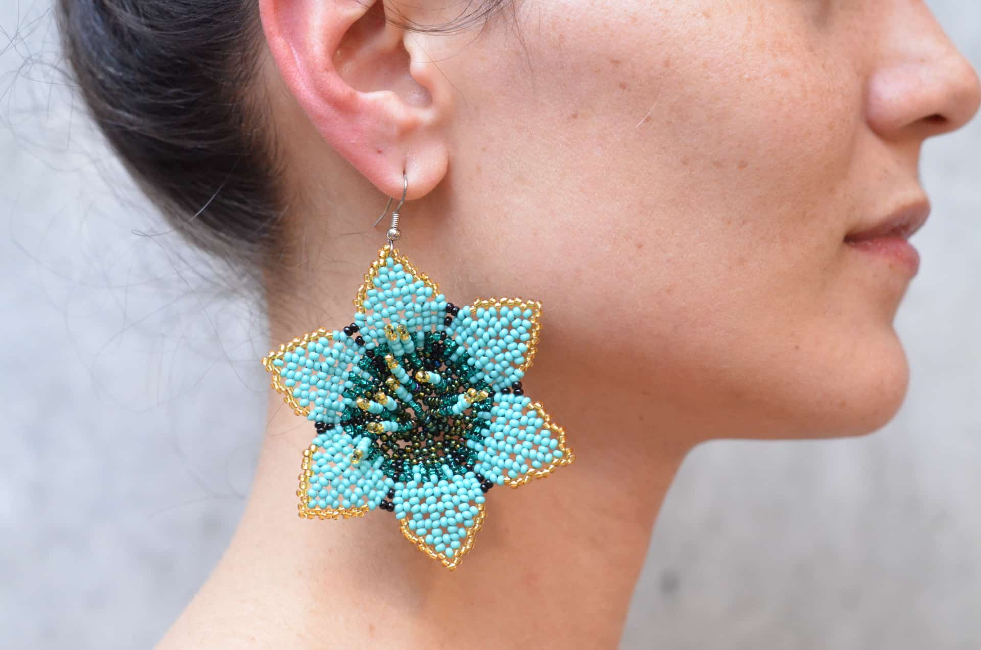 A woman wearing a star-shaped colorful earring